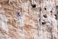 Greece, Kalymnos, woman climbing in rock wall - ALRF00902