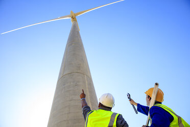 Low angle view of technicians in front of wind turbine - ZEF14965