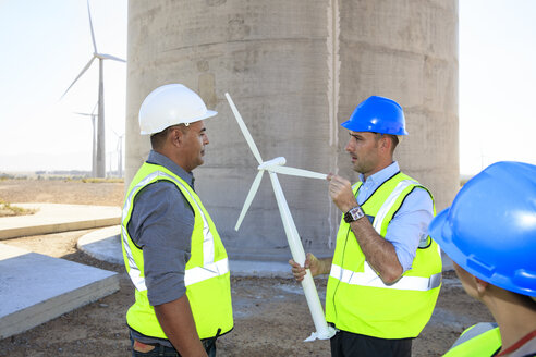 Three engineers with wind turbine model discussing on a wind farm - ZEF14968