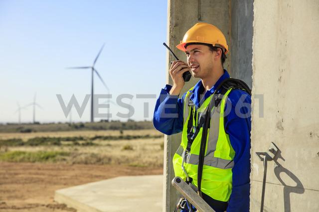 Technician using walkie-talkie at wind turbine - ZEF14971