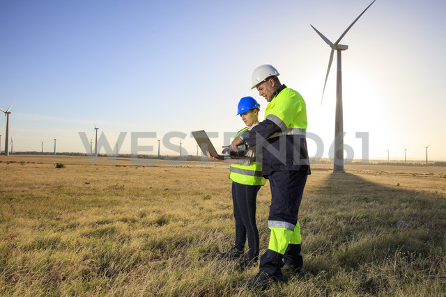 Two engineers with laptop discussing on a wind farm - ZEF14980