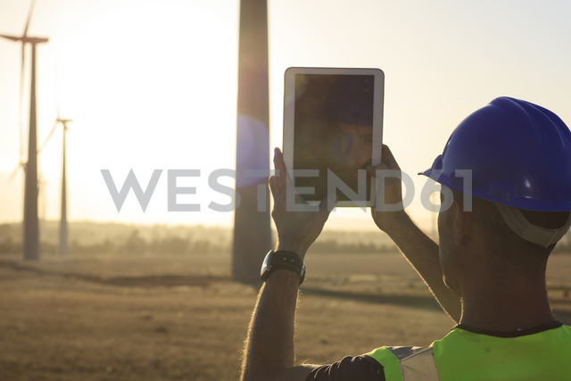 Engineer taking picture with a tablet of a wind farm at sunset - ZEF14986