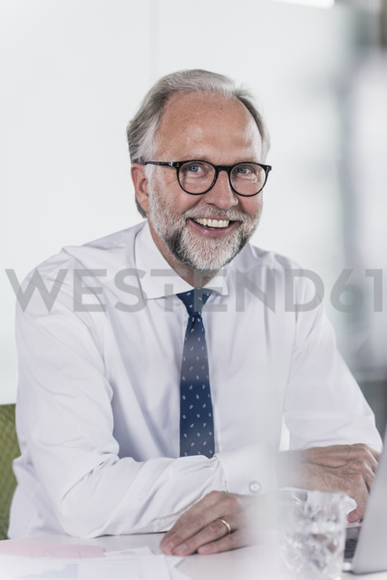 Portrait of happy mature businessman sitting at desk in office - UUF12724