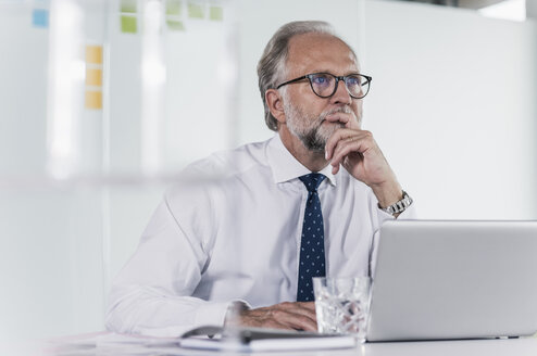 Mature businessman with laptop at desk in office thinking - UUF12727