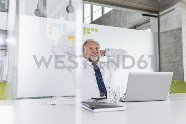 Smiling mature businessman at desk in office leaning back - UUF12733