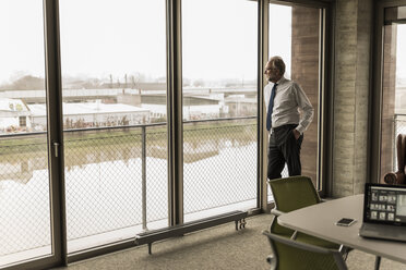 Serious mature businessman standing at the window looking out - UUF12736