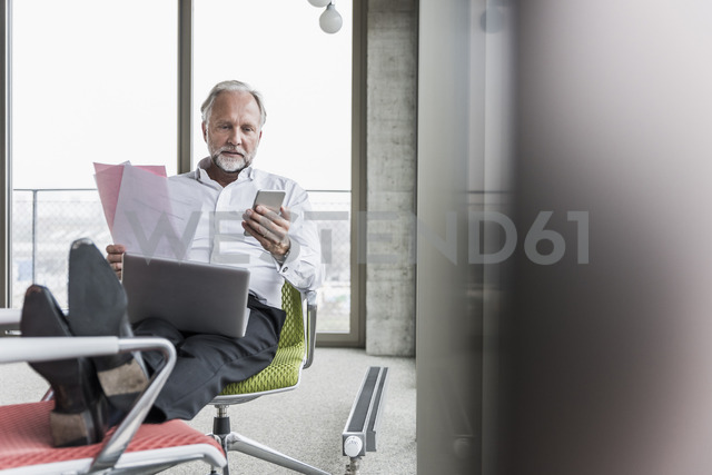 Mature businessman working on office chair with feet up - UUF12748