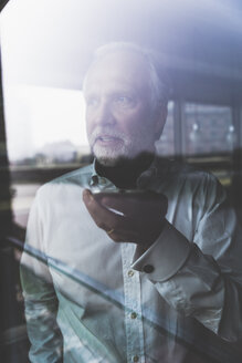 Portrait of mature businessman at the window using cell phone - UUF12751