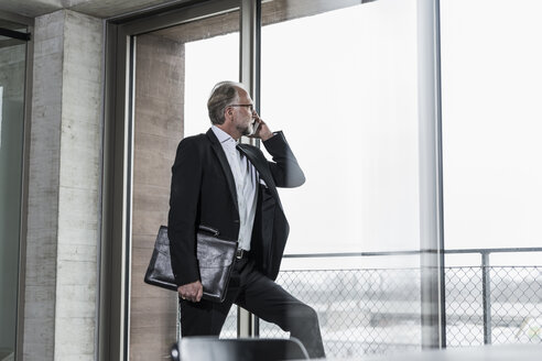 Mature businessman at the window talking on cell phone - UUF12754
