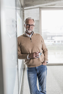 Portrait of casual mature businessman standing in office - UUF12763