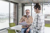 Casual mature businessman discussing papers with young woman in conference room in office - UUF12769