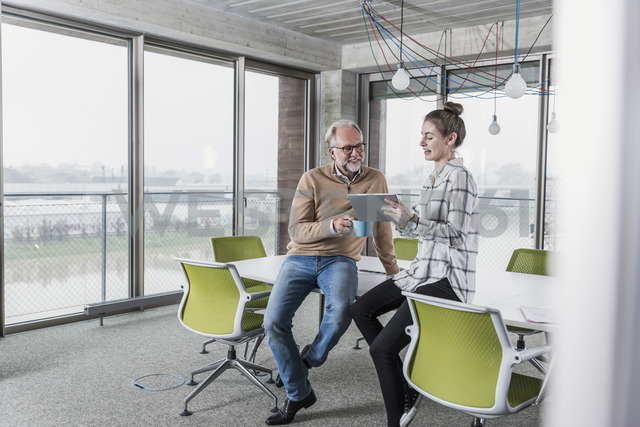 Casual mature businessman and young woman with tablet in conference room in office - UUF12772