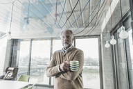 Casual mature businessman looking at data at glass pane in office - UUF12778