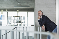 Portrait of mature businessman leaning on railing - UUF12781