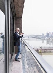 Happy mature businessman standing on balcony cheering - UUF12793
