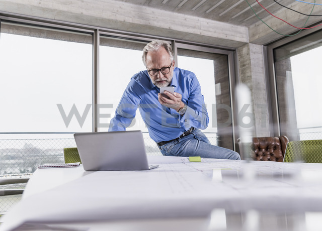 Mature businessman using laptop and smartphone in conference room in office - UUF12799