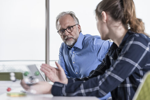 Mature businessman and young woman with atomic model talking in conference room - UUF12805