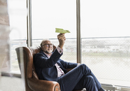 Smiling mature businessman sitting in leather armchair holding paper plane - UUF12817