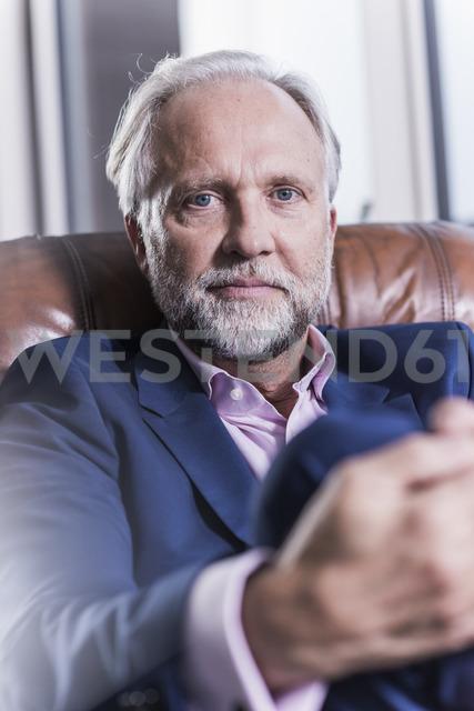 Portrait of mature businessman sitting in leather armchair - UUF12820