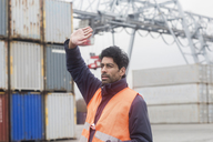 Man wearing reflective vest working at container port - SGF02183