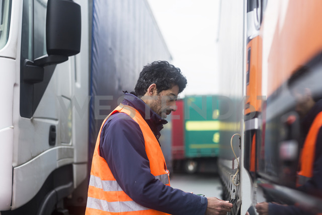 Man wearing reflective vest examining truck - SGF02186