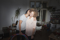 Couple embracing while standing against wall at home - FSIF01030