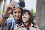 Smiling man taking selfie with young female friend - FSIF01087