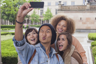 Young man making face while taking selfie with female friends, Berlin, Germany - FSIF01090
