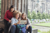 Portrait of young female tourists sitting with map at Altes Museum against Berlin Cathedral, Germany - FSIF01096