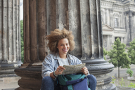 Portrait of smiling young Afro female tourist sitting with map against column at Altes Museum - FSIF01102
