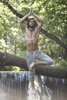 Young man standing in tree pose on log against waterfall at forest - FSIF01108