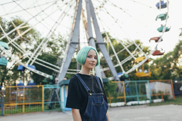 Portrait of smiling teenage girl standing against Ferris wheel at park - FSIF01114