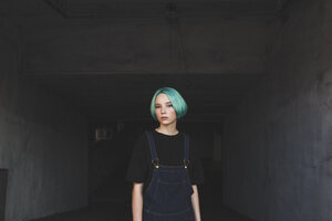 Portrait of teenage girl standing in basement - FSIF01120