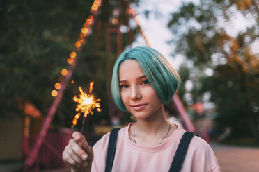 Portrait of teenage girl holding illuminated sparkler - FSIF01123