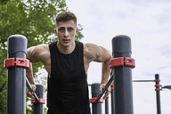 Low angle view of young male athlete exercising on parallel bars against sky - FSIF01159