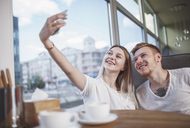 Happy young couple taking selfie with mobile phone while sitting at restaurant - FSIF01171