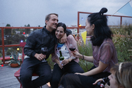 Happy man embracing woman while sitting with friends on patio at dusk - FSIF01174