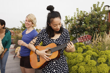 Young woman playing guitar on patio while female friends standing in background - FSIF01177