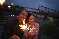 Happy couple holding sparklers on patio at night - FSIF01183