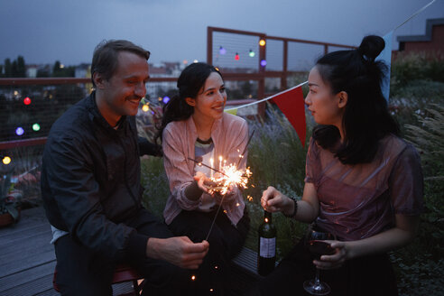 Happy male and female friends holding sparklers on patio - FSIF01186