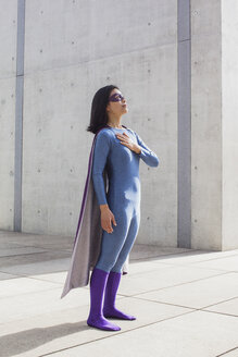 Confident woman wearing superhero costume standing on floor by wall - FSIF01198