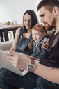 Smiling parents with daughter looking at laptop while sitting on sofa at home - FSIF01210