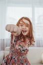 Portrait of cheerful girl punching while standing against sofa in living room - FSIF01213