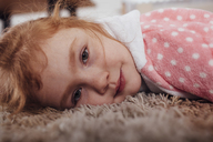 Close-up portrait of girl lying on carpet at home - FSIF01216