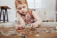Girl playing with puzzle pieces while lying on carpet at home - FSIF01225