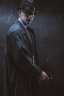 Portrait of confident man holding gun standing against black wall - FSIF01228