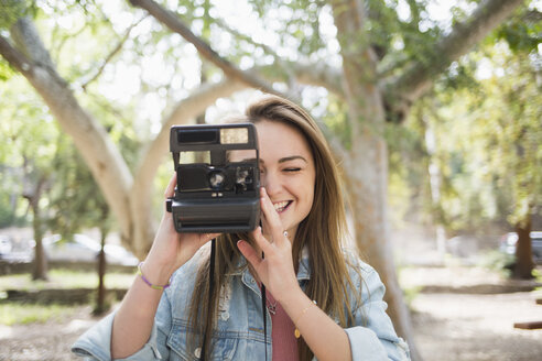 Happy young woman using instant camera at park - FSIF01240