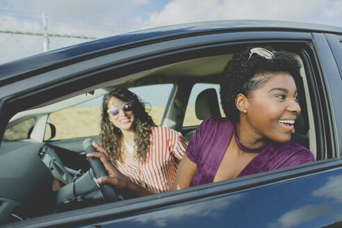 Smiling young woman looking away while sitting with female friend in car - FSIF01252