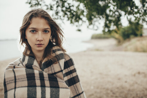 Portrait of teenage girl wrapped in blanket by lakeshore - FSIF01264