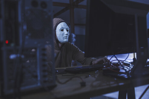 Man wearing mask and hood using computer at table - FSIF01282